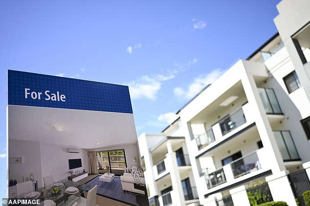 The best time to start saving for your own home is right now according to property experts. Pictured: A real estate advertising board is seen next to a newly built unit in Canberra