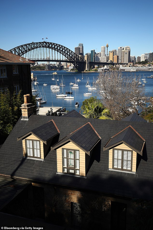 A house is pictured by the waterfront with the Sydney Harbour Bridge seen in the distance