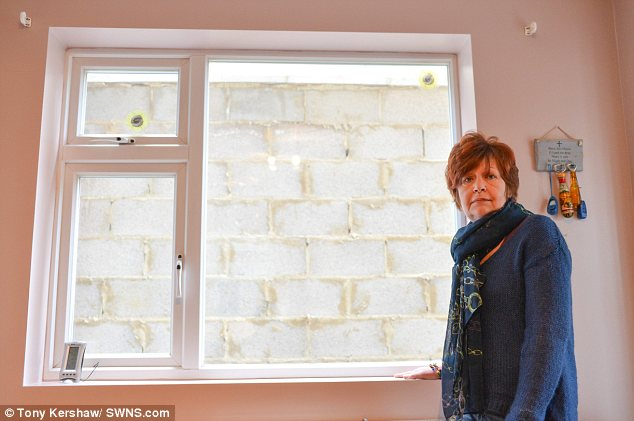 Room with no view: Helen Coughlan posing in front of her upstairs landing window where next-door neighbour Tariq Ahmed has built a wall without planning permission
